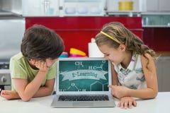Crianças que olham um computador com ícones da escola na tela Imagens de Stock Royalty Free