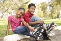 Crianças que põr sobre na linha patins no parque imagens de stock royalty free