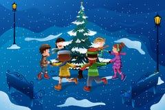 Crianças que patinam em torno de uma árvore de Natal Fotografia de Stock