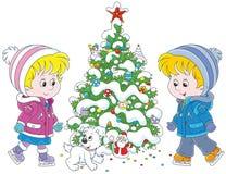 Crianças que patinam em torno de uma árvore de Natal Foto de Stock Royalty Free