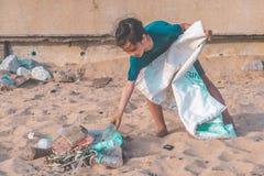 Crianças que pegaram a garrafa e o gabbage plásticos que encontraram na praia para o conceito ascendente limpo ambiental imagens de stock royalty free