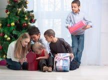 Crianças que prendem presentes do Natal imagem de stock