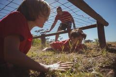 Crianças que rastejam sob a rede durante o treinamento do curso de obstáculo fotos de stock