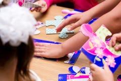 Crianças que resolvem o enigma de serra de vaivém Fotos de Stock Royalty Free