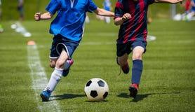 Crianças que retrocedem o fósforo de futebol na grama Jogo de futebol da juventude Menino Imagens de Stock Royalty Free