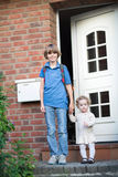 Crianças que saem em casa no primeiro dia à escola Foto de Stock Royalty Free