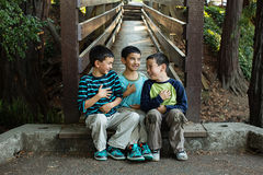 Crianças que sentam junto giggling Fotografia de Stock Royalty Free