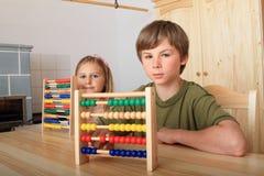 Crianças que sentam-se atrás da tabela de madeira com ábacos fotografia de stock royalty free