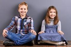 Crianças que sentam-se com pés cruzados Imagens de Stock Royalty Free