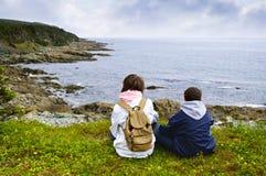 Crianças que sentam-se na costa atlântica em Terra Nova fotografia de stock