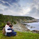 Crianças que sentam-se na costa atlântica em Terra Nova Imagens de Stock Royalty Free