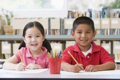 Crianças que sentam-se na mesa e que escrevem na sala de aula