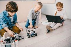 crianças que sentam-se no assoalho na classe da educação da haste com robôs fotografia de stock