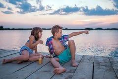 Crianças que sentam-se pelo rio e que têm o divertimento imagem de stock