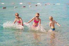 Crianças que têm o divertimento na água no beira-mar Fotos de Stock