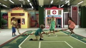 Crianças que têm o divertimento no centro do lazer das crianças vídeos de arquivo