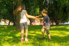 Crianças que têm o divertimento no parque, na rotação e no jogo imagens de stock