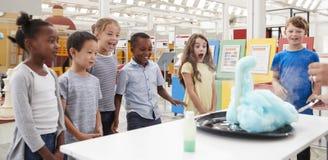 Crianças que têm o divertimento que olha uma experiência em um centro da ciência fotografia de stock