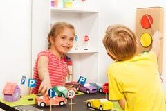 Crianças que têm o divertimento que joga com carros e modelos dos sinais Fotografia de Stock Royalty Free