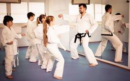 Crianças que tentam movimentos marciais na classe do karaté imagens de stock