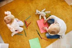 Crianças que tiram no papel ao sentar-se no assoalho fotos de stock royalty free
