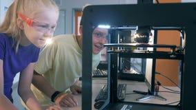 Crianças que trabalham com a impressora 3D Menino e menina que trabalham em um laboratório de ciência com equipamento de impressã video estoque
