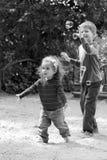 Crianças que travam bolhas de sabão no campo de jogos do verão Fotografia de Stock