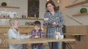 Crianças que usam o gelado de júbilo do telefone no café filme