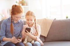 Crianças que usam Smartphones em casa imagem de stock royalty free