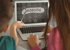 Crianças que usam um computador com ícones da escola na tela Fotos de Stock Royalty Free