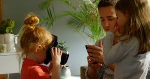 Crianças que vestem auriculares da realidade virtual com o pai na sala de visitas 4k video estoque