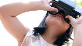 Crianças que vestem vidros da realidade virtual com o divertimento e a posição surpreendente da cara exteriores filme