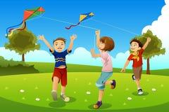 Crianças que voam papagaios em um parque Imagens de Stock