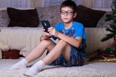 crianças, tecnologia, comunicação do Internet e conceito dos povos - menino com mensagem texting do smartphone ou do jogo jogo em foto de stock