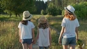 Crianças três meninas nos chapéus que guardam as mãos que andam para trás ao longo da estrada secundária rural video estoque