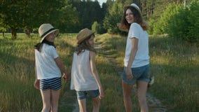 Crianças três meninas nos chapéus que guardam as mãos que andam para trás ao longo da estrada secundária rural filme