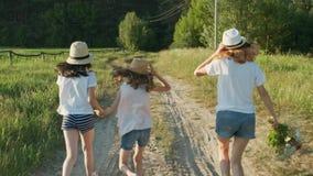Crianças três meninas nos chapéus que guardam as mãos que correm para trás ao longo da estrada secundária rural filme