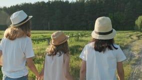 Crianças três meninas nos chapéus que guardam as mãos que correm para trás ao longo da estrada secundária rural video estoque