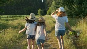 Crianças três meninas nos chapéus que guardam as mãos que correm para trás ao longo da estrada secundária rural vídeos de arquivo