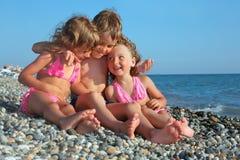 Crianças três que sentam-se junto na praia rochoso Imagem de Stock Royalty Free