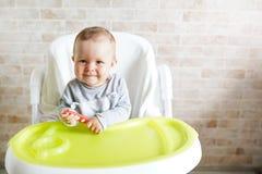A crian?a alegre do beb? come o alimento pr?prio com colher Retrato da criança feliz na cadeira alta na cozinha ensolarada Fundo  imagens de stock royalty free