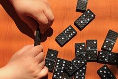 Crian?as de ensino para jogar o jogo dos domin?s em um fundo de madeira fotos de stock