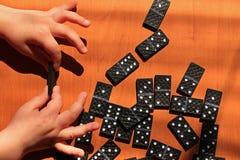 Crian?as de ensino para jogar o jogo dos domin?s em um fundo de madeira fotografia de stock