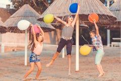 Crian?as felizes com os bal?es da cor que saltam no Sandy Beach imagem de stock royalty free