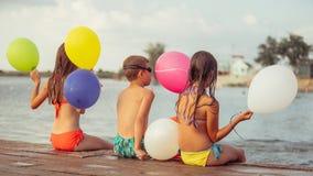 Crian?as felizes que guardam bal?es da cor ao sentar-se na praia imagens de stock