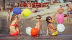 Crian?as felizes que guardam bal?es da cor na praia imagem de stock