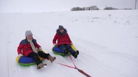 Crian?as felizes que sledding no inverno na neve e que acenam suas m?os as crian?as riem e exultam menina que joga no inverno filme