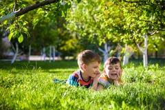 Crian?as felizes que t?m o divertimento ao ar livre Crian?as que jogam no parque do ver?o Rapaz pequeno e seu irm?o que colocam n imagens de stock