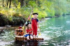 Crian?as que jogam a aventura do pirata na jangada de madeira imagens de stock royalty free