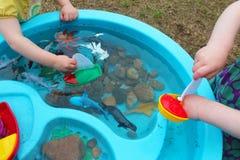 Crian?as que jogam com os brinquedos da vida dos barcos e da criatura/oceano do mar em uma tabela de ?gua imagem de stock